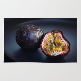 Halved Passion fruit on black plate Rug