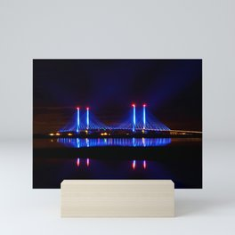 The Indian River Inlet bridge reflecting off the bay as beams of blue light penetrate the night sky Mini Art Print