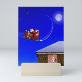 Young girl watching Santa Claus fly over her house Mini Art Print