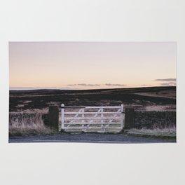 White gate leading to moorland at twilight. Derbyshire, UK. Rug