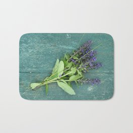Bouquet of violet flowers on a painted green bench Bath Mat