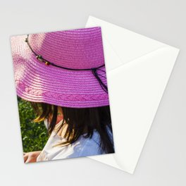 Big pink hat for a child girl on the grass Stationery Cards