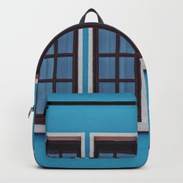 CLEAR GLASS WINDOWS IN BLUE CONCRETE WALL Backpack