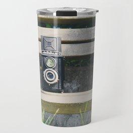 two vintage cameras sitting on a park bench ... Travel Mug