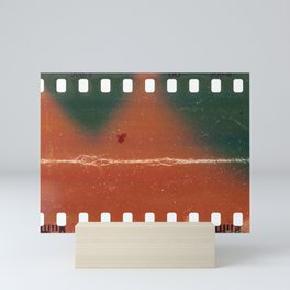 Start of 35mm negative filmstrip, first frame on white background, real scan of film material with cool scanning light interferences and hard scratches. Mini Art Print