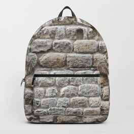 Close up view of the textured stone wall of a historical building Backpack