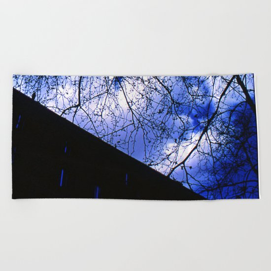 Urban maple tree in a winter evening with a city building and a cloudy sky Beach Towel