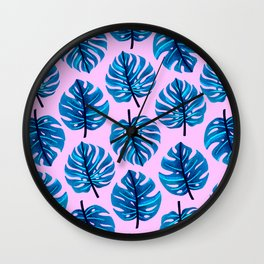 Blue monstera leaves pattern on pink background Wall Clock