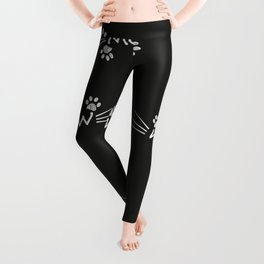Meow text with doodle cat paw prints black background Leggings