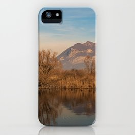 Tree in the foreground and mountains in the background are reflected in the river water iPhone Case