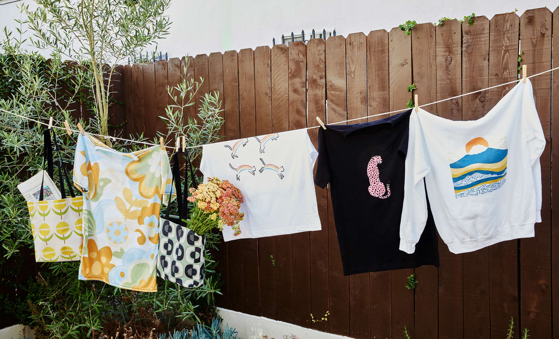t-shirts, hoodies and tote bags on a clothesline