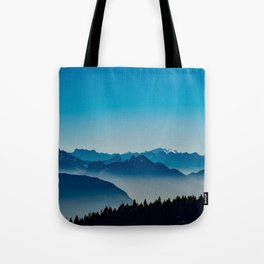 Rise above the mist. Blue Tote Bag