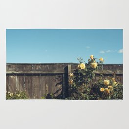 Yellow flowers over a wooden fence Rug