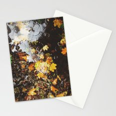 Detail of autumnal leaves and rain in a puddle. Norfolk, UK Stationery Cards