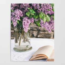 Romantic photo composition with lilac and vintage book on white lace tablecloth. Poster