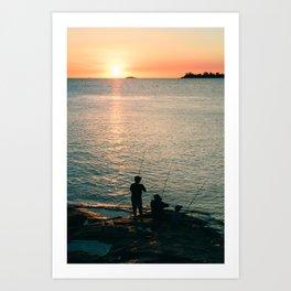Three fisherman enjoy a beautiful sunset at the shore of 'Colonia del Sacramento, Uruguay'. Art Print