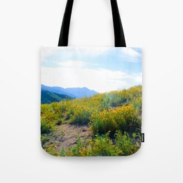 yellow poppy flower field with green leaf and blue cloudy sky in summer Tote Bag