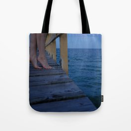 Woman standing on the edge of a pier Tote Bag