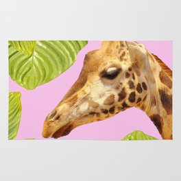 Giraffe with green leaves on a pink background Rug
