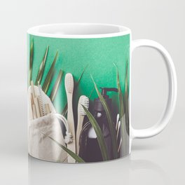 Zero waste concept. Cotton bag, bamboo cultery, glass jar, bamboo toothbrushes, hairbrush and straws on green background Coffee Mug