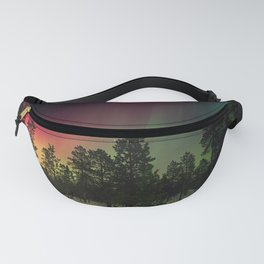 Rainbow colors of northern lights in pine forest at midnight Fanny Pack
