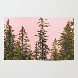 Tall trees against pink sky Rug