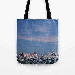 Last light on snowy mountain peaks. Tote Bag