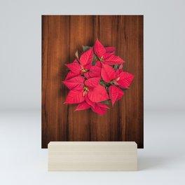 Red Christmas flower on brown wood Mini Art Print
