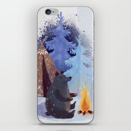 A teddy bear with a wigwam warms its paws by the fire in winter. iPhone Skin