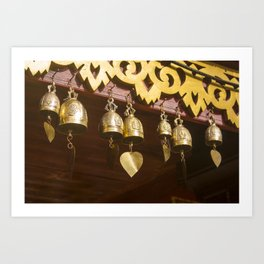 Golden glow on copper bells with clapper hearts, hanging from wooden ceiling. Art Print
