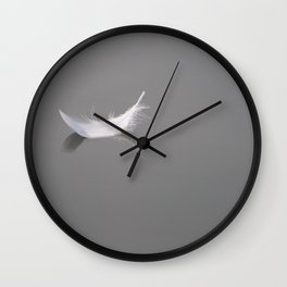 Swan feather drifting on the river Wall Clock