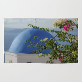 Blue dome church and flowers in Santorini, Greece Rug