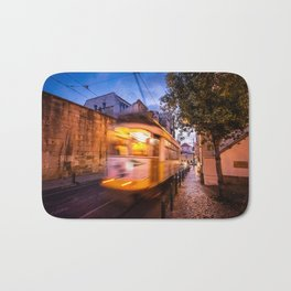 A tram transports tourists through the Alfama District in Lisbon, Portugal at dusk Bath Mat