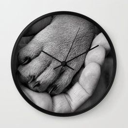 The greatness of a nation can be judged by the way its animals are treated; paw of a puppy in a woman's hand black and white photograph - photographs - photography Wall Clock