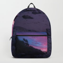 sunset over the calm water and rocky shore Backpack