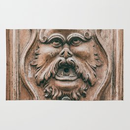 Face with beard carved on ancient door in Pisa Tuscany Italy Rug