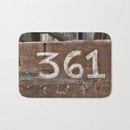 Numbers on rusty door Bath Mat
