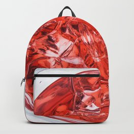 Glass with Ice and Red Liquor - top view Backpack