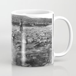 Man with rifle stands in mountain stream as it floods, east of Palmdale, California, ca.1920 Coffee Mug