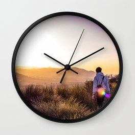 Man at the top of a mountain against foggy landscape. Winter outdoor activities. Wall Clock