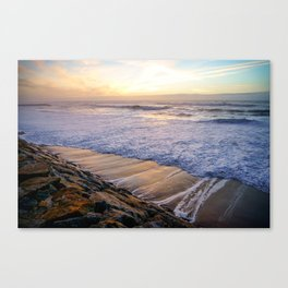 White waves crashing into mossy rocks, with a beautiful autumn sunset. Canvas Print