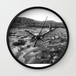 Man with rifle stands in mountain stream as it floods, east of Palmdale, California, ca.1920 Wall Clock