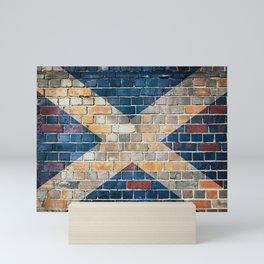 Scotland flag on a brick wall Mini Art Print