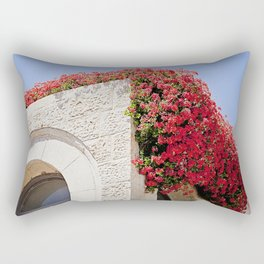 Vibrant Red Flowers Over Stone Building Rectangular Pillow