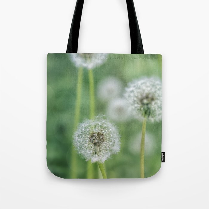 Dandelion flower on green meadow Tote Bag