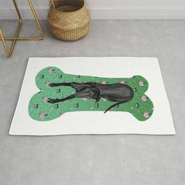 Black Greyhound Puppy on a Green Bone-shaped Carpet Rug