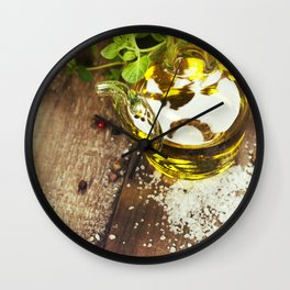 Olive oil,  herbs and spices on a wooden table Wall Clock