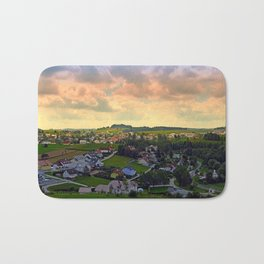 Beautiful village skyline beyond cloudy sky | landscape photography Bath Mat