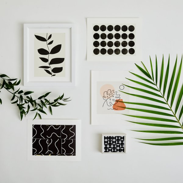 black and white abstract art prints surrounded by plants
