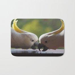 Pair of cockatoos eating seed Bath Mat